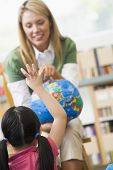 Teacher In Class Showing A Globe With Student Volunteering In Foreground (Selective Focus)