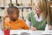 picture of student teacher  - Student in class reading with teacher - JPG