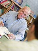 Two Men In Library With Notepads Talking (Selective Focus)