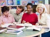 Three Women Sitting In Library With Books And Notepads While A Man Leans Over Them (Selective Focus)