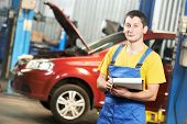 repairman auto mechanic with clipboard in front of modern car during automobile maintenance at engin