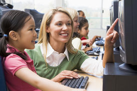 image of student teacher  - Teacher helping student at computer terminal with students in background  - JPG