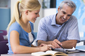 stock photo of student teacher  - Teacher giving personal instruction to female student - JPG