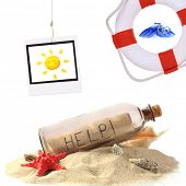 Glass bottle with note inside, lifebuoy and photo of sun isolated on white