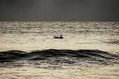 Surfer floating on surf board alone in the sea.