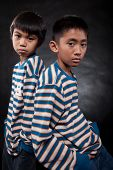 pic of fraternal twins  - Two young eleven year old asian boys standing with backs together wearing matching shirts - JPG