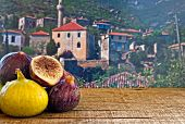 Fresh Figs On Rustic Wooden Table Against Village Background