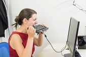 stock photo of revenge  - Angry businesswoman biting the keyboard at her office - JPG