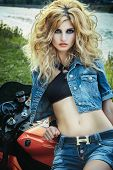 Sexy woman in rock style on a motorcycle