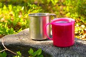 Two Touristic Cups Metal And Pink Plastic With Tea On Stone In Forest Picnic Thematic