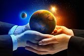 Close up image of human hands holding earth planer. Ecology concept. Elements of this image are furn