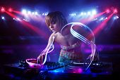 Pretty young disc jockey girl playing music with light beam effects on stage