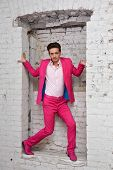 Young man in pink suit and shoes stands with in wall aperture in strange pose