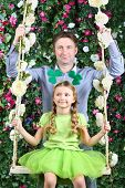 Happy father and little girl with shamrock on head on swing in garden next to verdant fence.