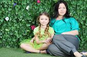 Beautiful mother and little girl sit on grass in garden next to verdant fence.