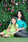 Smiling mother and little daughter sit on grass in garden next to verdant fence.