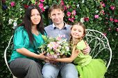 Happy family of three sit on bench, hold flowers and look at camera in garden near verdant hedge.