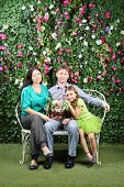 Happy family of three sit on bench with bunch of flowers in garden near verdant hedge.