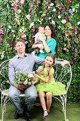 Smiling family of four sit on white bench with bunch of flowers and stand behind in garden near verd