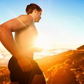 Running people - male runner at sunset in mountain. Man athlete jogging training for marathon trail run in beautiful amazing landscape nature above the clouds. Fit shirtless male cross country runner.