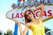 Tourist woman in Las Vegas sign posing happy. Asian mixed race tourists girl having fun in front of Welcome to Fabulous Las Vegas sign in beautiful yellow summer dress. Nevada, USA.