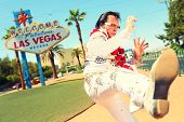 Elvis look-alike impersonator man in front of Welcome to Fabulous Las Vegas sign on the strip. People having fun and Viva Las Vegas concept image with Elvis impersonator doing some crazy moves.