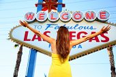 Welcome to Fabulous Las Vegas sign. Woman tourist happy standing with arms raised out looking at Las Vegas sign, Nevada, USA.