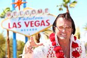 Elvis impersonator man in front of Las Vegas on the strip pointing looking at camera. People having