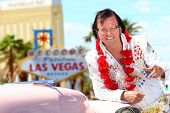 Las Vegas Elvis impersonator on the strip pointing looking at camera in front of Welcome to Fabulous