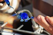 Delicate work of the glass blower. The Artist-glass blower produces a graceful tiny figure of an elephant from color glass