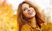 stock photo of cheer-up  - Beautiful autumn woman in golden park - JPG
