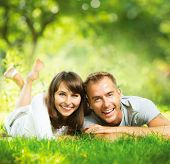 stock photo of mood  - Happy Smiling Couple Together Relaxing on Green Grass - JPG