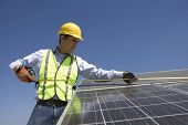 Young maintenance worker measuring solar cells on rooftop
