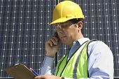 Young maintenance worker using cell phone while looking at clipboard near solar panels