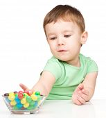 Little boy refusing to eat colorful candies, isolated over white