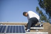 Full length side view of an African American man fixing solar panel on rooftop