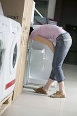 Side view of young woman examining refrigerator in shopping centre