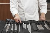 Midsection of male chef selecting knife sharpener out of full set in commercial kitchen