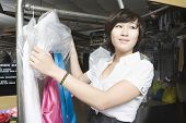 Happy young woman unwrapping plastic from dry cleaned clothes in laundry