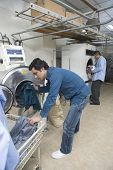 Full length of young men loading clothes in washing machine at laundry