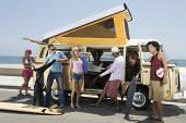 stock photo of campervan  - Multiethnic group of young people by campervan - JPG