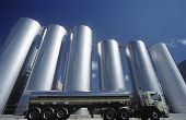 stock photo of tank truck  - Milk transport truck parked alongside storage tanks - JPG