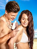Couple  applying sunblock at beach. Summer outdoor.