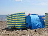 Unseen people relaxing behind wind breaks on Bridlington beach.