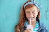 Niedliche Rothaarige Kind Konsummilch auf Vintage blau Hintergrund