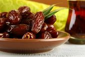Dried dates on plate with cup of tea on table on fabric background