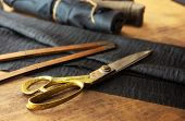 stock photo of tailoring  - Measuring and cutting textile or fine cloth - JPG