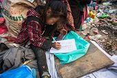 KATHMANDU, NEPAL - DEC 19: Unidentified child is sitting while her parents are working on dump, Dec