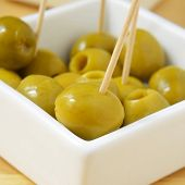 a bowl with olives with toothpicks served as tapas
