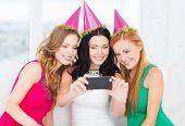 celebration, friends, bachelorette party, birthday concept - three smiling women in pink hats having
